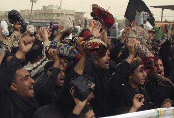 Iraqi Shi'ites wave the mats they use while praying as they protest in Baghdad's Sadr city