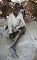 An elderly Chadian man sits in his tent in N'Djamena