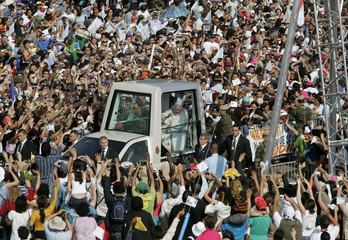 Catholics greet Pope Benedict XVI as he arrives in his popemobile to celebrate an open air mass in front of the Basilica of Our Lady of Aparecida in Aparecida