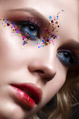 A young girl with a short haircut and bright creative makeup. A beautiful model with sparkles on the face and red lips. Evening makeup, beauty of the face. Close-up portrait.