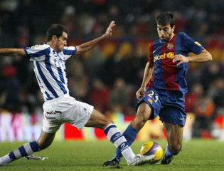 Barcelona's player Oleguer Presas fights for the ball against Real Sociedad's Gaizka Garitano during their Spanish First Division soccer match at Nou Camp stadium in Barcelona