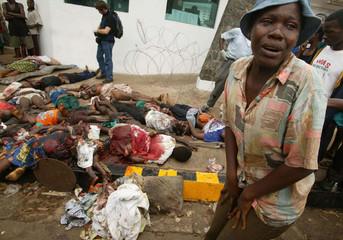 LIBERIAN WOMAN WEEPS NEAR PILE OF BODIES NEXT TO US EMBASSY INMONROVIA.