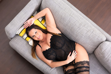 Big and beautiful woman relaxing in lingerie on the Sofa