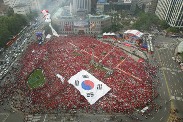 Soccer fans carry large flag as they gather to cheer for South Korean World Cup team in Seoul