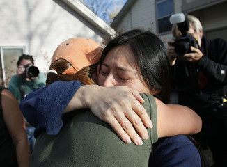 Mayumi Heene, mother of six-year-old Falcon, is hugged by a neighbor outside her house in Fort Collins