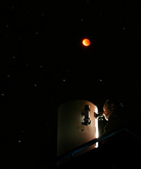 Chilean man observes the moon during lunar eclipse over Mamayuta hill Observatory in Chile.