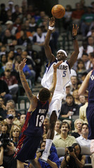 Mavericks guard Howard passes from the baseline as he is defended by Cavaliers guard West in Dallas