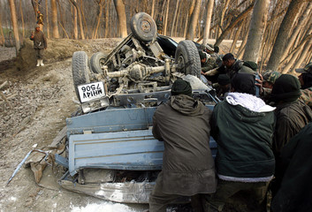 Indian policemen push the wreckage of their vehicle after a landmine blast in Bandiun