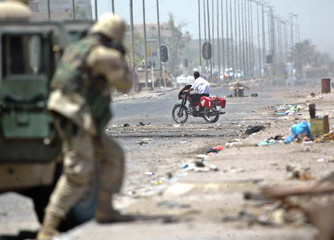 U.S. soldier takes aim down street at man riding motorcycle during firefight in Baghdad.