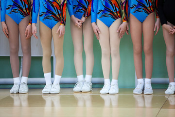 Kids feet of young gymnasts in white sports sneakers and color costumes stand in line in the gym floor