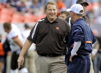 Cleveland Browns head coach Eric Mangini smiles while talking with Denver Broncos head coach Josh McDaniels prior to the start of their NFL football game in Denver, Colorado