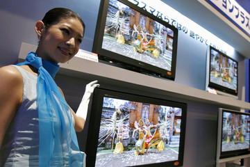 Model poses for pictures next to Panasonic's new 1080p resolution Viera 42-inch plasma televisions 'TH-42PZ700SK' during its launch event in Tokyo