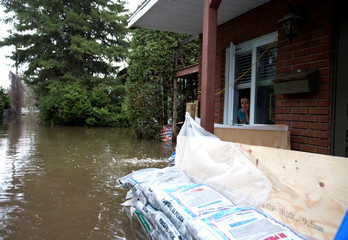 Emmanuelle St-Denis looks at the water levels from her home in a flooded residential neighbourhood in Ile Bizard, Quebec, Canada