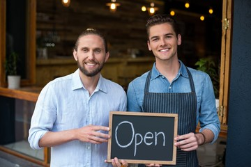 Man and waiter holding chalkboard with open sign