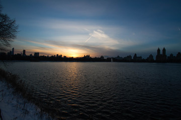 Blurred sunset over buildings and lake in New York