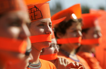 Israeli right-wing activists cover their mouths with orange ribbon in front of defence minister's ...