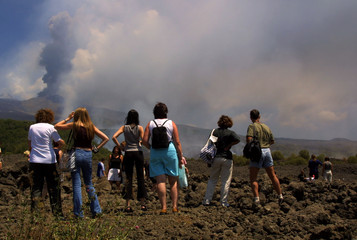 A GROUP OF TOURIST LOOK THE BLACK SMOKE COLUMN FROM MOUNT ETNA'SCRATER.