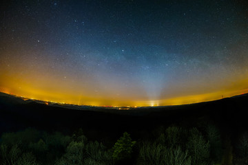 Astro Landscape with the Milky Way, the Zodiacal Light, and city lights as seen from the Luitpold Tower in the Palatinate Forest in Germany.