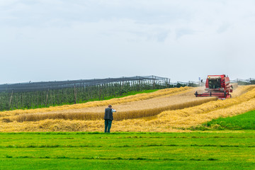 a combine harvester is working on a field in switzerland