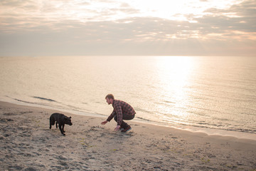 man playing with black puppy on the beach