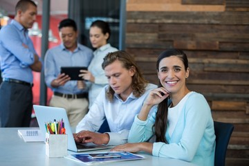 Portrait of businesswoman smiling while colleague using laptop
