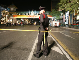 Policeman stands guard after bomb blasts in Bangkok