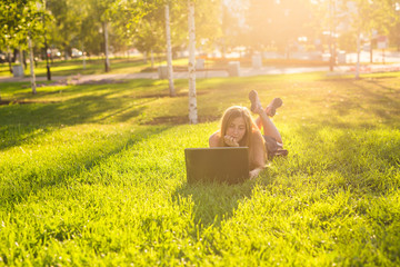 portrait of a beautiful student girl with laptop computer on the green grass in the park in spring time.