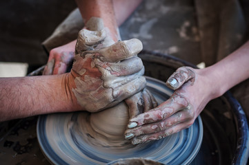 Woman and man hands. Potter at work. Creating dishes. Potter's wheel. Dirty hands in the clay and the potter's wheel with the product.