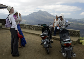 TOURISTS TAKE PICTURES AT OVERLOOK NEAR GUNUNG BATUR VOLCANO ON BALI.