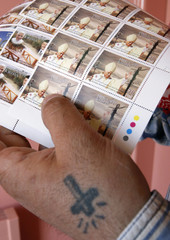 Jordanian man buys stamps with images of Pope Benedict XVI and Jordan's King Abdullah at a post office branch in Amman