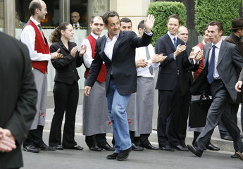 France's newly-elected President Nicolas Sarkozy leaves the Fouquet's Hotel in Paris