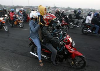 A family rides their motorcycle at Karawang regency