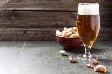 glass of light cold frothy beer, nuts on an old wooden background
