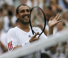 Baghdatis of Cyprus celebrates winning his match against Australia's Hewitt at the Wimbledon tennis championships