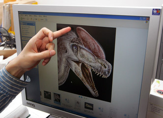 Xu, the head of Chinese researchers, points at a picture of a tyrannosaur in Beijing