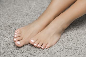 женские ноги с педикюром на полу и орхидеей