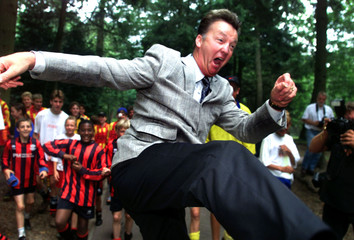 Dutch national soccer coach Louis van Gaal performs a karate kick at the request of gathered youth p..
