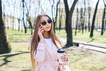 Fashionable woman with phone and cofee in the city. Fashion woman in a sunglasses and pink jacket outdoor