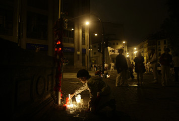 A boy places a candle at the place where Spanish runner Jimeno was gored to death in Pamplona