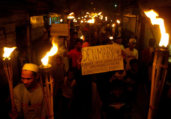 Filipino Muslims hold up torches during a rally outside a mosque in Manila