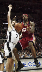 Cleveland Cavalier James goes to basket against San Antonio Spurs' Oberto during their NBA basketball game in San Antonio