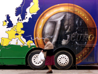 An old woman walks past a bus decorated with an Euro coin and a map showing the euro-zone countries ..