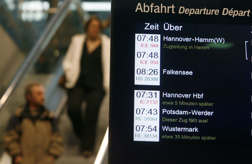 People walk past a display of German railway operator Deutsche Bahn AG showing cancelled and delayed trains at Berlin's Hauptbahnhof central station