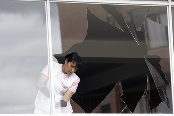 Woman removes pieces of glass near the site where a small bomb exploded in Bogota