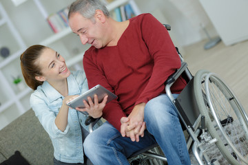 Young lady showing tablet screen to man in wheelchair