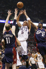 New Jersey Nets Kidd gets off shot under pressure from Cleveland Cavaliers Ilgauskas and Hughes in East Rutherford