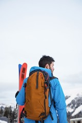 Skier standing with ski on snow covered mountains