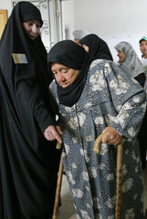 A member of Lebanon's Hizbollah group helps an old woman at a polling station in Jabsheet village ...