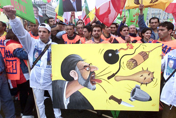 Exiled Iranian demonstrators carry a poster with a cartoon of Iranian President Mohammad Khatami dur..
