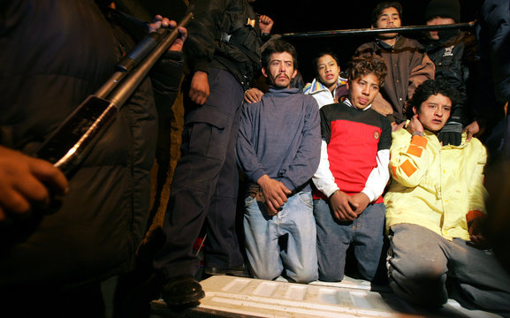 Mexican police stand guard next to suspected burglars in a village in the Naucalpan district